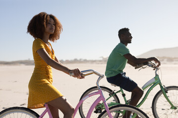 Mixed race couple riding bikes on the beach