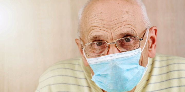 old man in disposable mask glasses and pullover at home