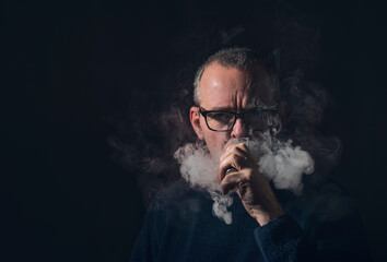 studio portrait of a man with vaporiser and glasses