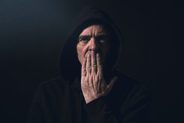 portrait of a man with a hoodie holding a hand in front of his mouth