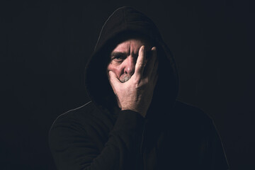 portrait of a man with a hoodie holding a hand in front of his face