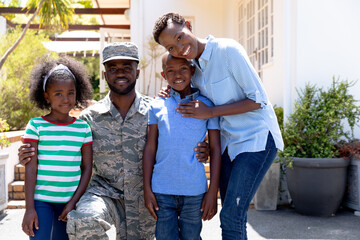African American male soldier wearing uniform and his family standing by their house