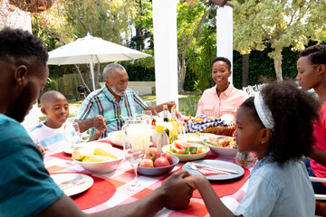 Senior African American couple and their family sitting by a table in the garden