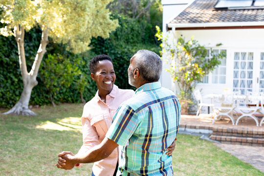 Senior African American couple dancing in their garden