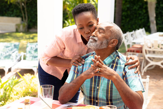 Senior African American woman kissing her husband during a family lunch in the garden
