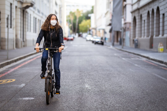 Caucasian woman wearing a protective mask and earphones, and biking in the streets