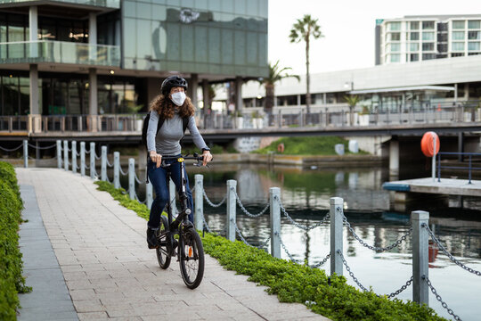 Caucasian woman wearing a protective mask and a cycling helmet in the streets, biking in the streets