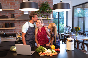 Caucasian family spending time in the kitchen and using a laptop