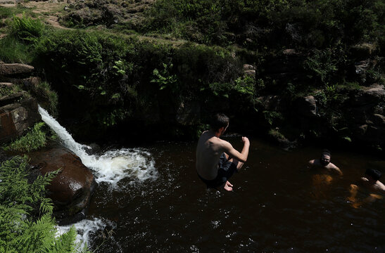 A man jumps into the water as he enjoys the hot weather at the Three Shires Head, the point where Cheshire, Staffordshire and Derbyshire meet