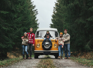 Group of young friends traveling by orange retro VW Bulli. Family vacation travel, holiday trip.