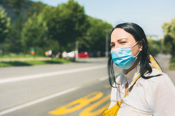 Woman wearing a  protective face mask, looking away and waiting for bus.  Concept of transport and city traffic during COVID-19 concept  Selective focus
