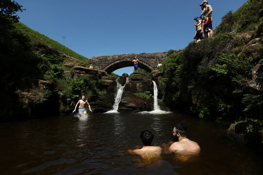 A boy jumps into the water as he enjoys the hot weather at the Three Shires Head, the point where Cheshire, Staffordshire and Derbyshire meet