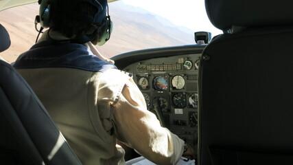 Pilot in einer Cessna (Kleinflugzeug) vor seinen Cockpitinstrumenten