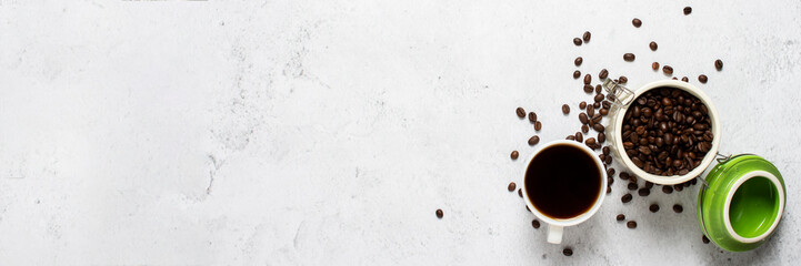 cup with coffee, a can of coffee beans and coffee beans are scattered on a concrete background. Banner. Concept of fresh coffee, breakfast, plantation. Top view, flat lay