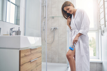 Attractive young woman using body massage roller in bathroom