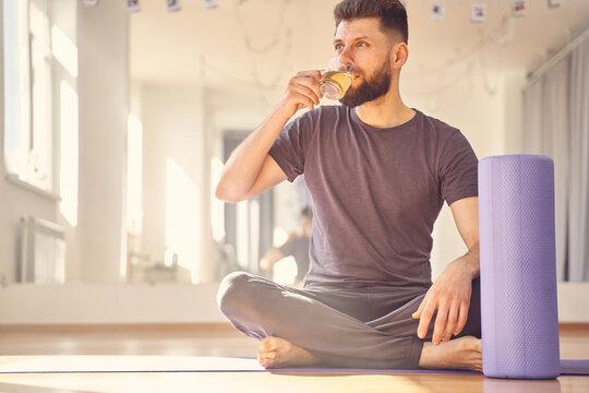 Handsome young man drinking tea in yoga studio