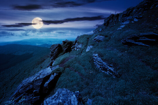 rock on the grassy slope at night. summer landscape in mountains in full moon light. ridge in the distance. clouds on the sky. challenging journey