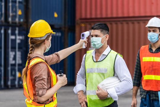 Engineer worker waring surgical mask checking body temperature using infrared digital thermometer check temperature before into work place, workers with protective mask