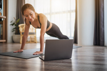A beautiful young asian woman doing push ups on training mat while watching online workout...
