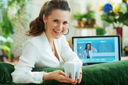 happy elegant female with tooth and opened digital dental site