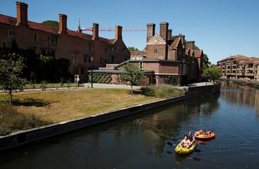 Men sit in a kayak as they tug a woman in a dinghy on a river, in Cambridge
