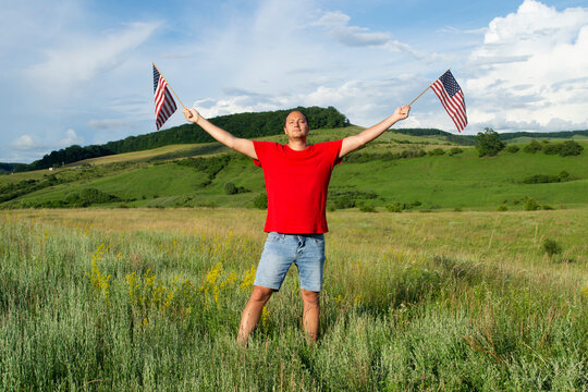 Young handsome attractive American man with two red white blue star striped USA US flags in hands outdoor celebrating Independence Day 4th 4 fourth of July after coronavirus lockdown pandemic covid-19