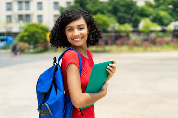 Laughing hispanic female college student with backpack