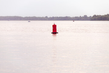 A red buoy on the Dnieper river in Kiev, Ukraine, for the safety and security of the boats travelling on the water. Selective focus