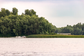 Little house close to the Dnieper river in Kiev, Ukraine, at the beginning of spring, under a cloudy sky. A blue and white speedboat passes in front of the tender green trees.
