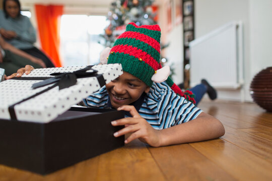 Excited boy opening Christmas gift on living room floor