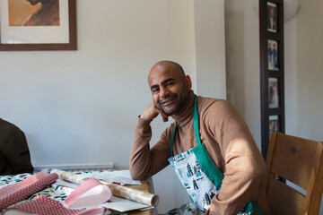 Portrait happy man in Christmas apron wrapping gifts at table