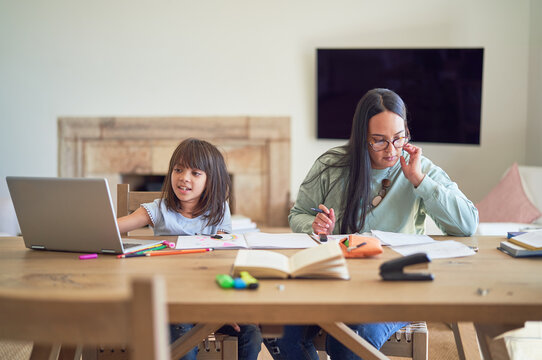 Mother paying bills next to daughter homeschooling at table