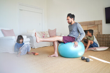 Father exercising in living room with kids