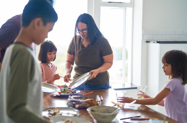 Family clearing food and dishes from lunch table
