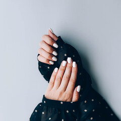 Female hands with white manicure on a gray background.
