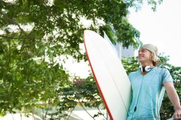 サーフボードを持つ若い男性