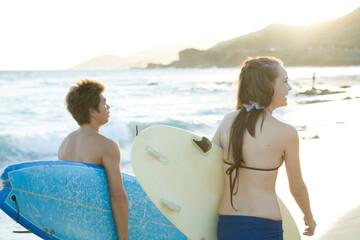 サーフボードを持つ若いカップル