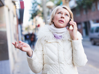 Mature woman is talking by phone in time walking
