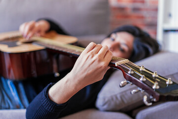 Woman playing guitar sitting on her couch at home and learning with online lessons and some masks are hanging due to containment. Behind it is a brick wall