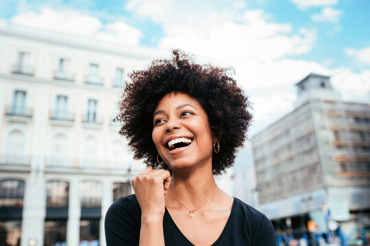 Afro young woman laughing while looking away in the street