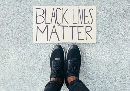 Feet detail besides a Black Lives Matter sign on floor. A a gesture against racism
