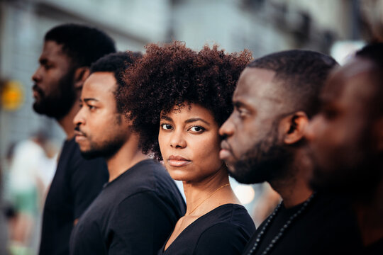 Black people on street with serious expression. The woman is looking at camera