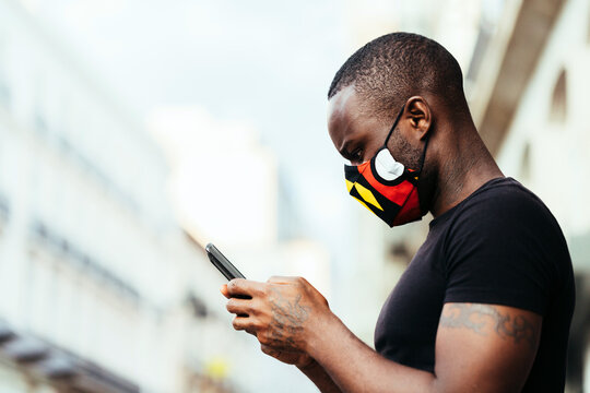 Closeup portrait of african american man wearing a colorful mask. He is using a cellphone with serious expression