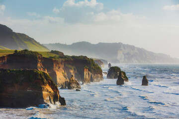 """Rock formations called """"three sisters"""" near Tongaporutu along the west coast of the North Island at sunset, New Zealand"""