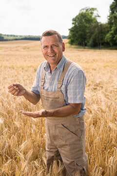 Portrait of happy farmer holding wheat while standing at field in farm