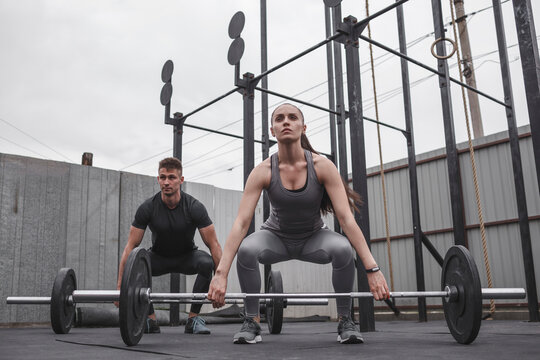 Full length of determined male and female athlete exercising with barbells during crossfit training