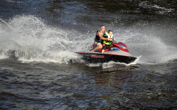 A man and a child ride a jet ski near Frodsham Watersports club, in Frodsham