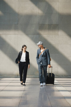 Full length of confident business people with wheeled luggage walking at airport