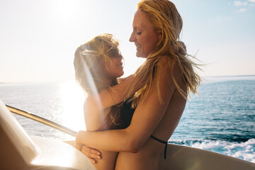 Mother and daughter on a yacht enjoying vacation