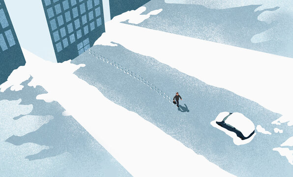 High angle view of man walking on snow covered road in city
